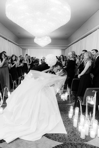 black-and-white-photos-of-groom-dipping-bride-for-a-kiss-at-the-end-of-aisle