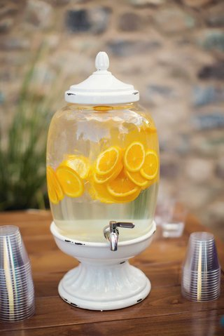white-distressed-drink-dispenser-with-silver-spout-and-ice-water-filled-with-orange-slices