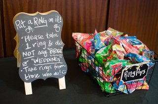 ring-pop-candies-in-a-basket-next-to-chalkboard-with-rules-of-game-for-a-bridal-shower