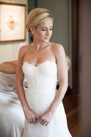an-excited-bride-gets-zipped-into-her-lace-monique-lhuillier-wedding-gown-by-one-of-her-bridesmaids