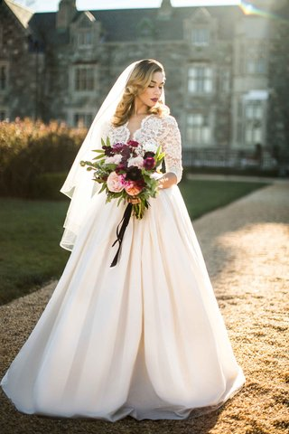 bride-ball-gown-bouquet-courtyard-ersa-atelier-wedding-dress-illusion-sleeves-full-skirt-veil
