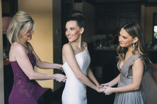 mother-of-the-bride-in-plum-dress-zipping-up-bride-in-wedding-dress-while-sister-holds-her-hand