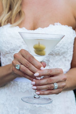diamond-wedding-band-and-emerald-cut-aquamarine-ring-holding-martini
