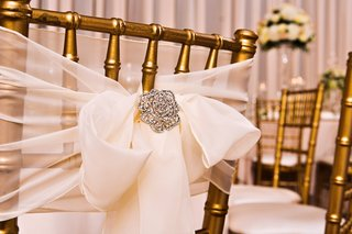 gold-chairs-with-sheer-white-bow-and-crystal-brooch