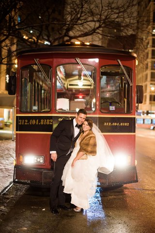 bride-in-fur-stole-white-wedding-dress-on-back-of-trolley-with-groom-in-tuxedo-bow-tie-chicago