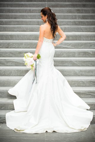 bride-in-white-trumpet-dress-turns-back-pink-white-and-green-bouquet-with-ribbons