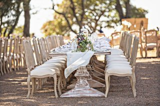 wedding-reception-outside-long-wood-pedestal-tables-with-wood-chairs-upholstered-linen-runner