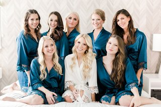bride-in-white-lace-trim-robe-long-blonde-hair-bridesmaids-on-bed-in-blue-robe-lace-trip-curled-hair
