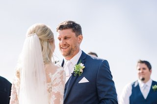 groom-smiling-at-bride-in-navy-blue-suit-at-wedding