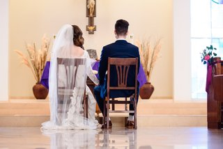 bride-and-groom-sit-in-wooden-chairs-at-catholic-ceremony