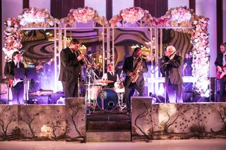 live-band-performs-at-reception-on-stage-with-mirrors-blush-pink-white-flower-decorations