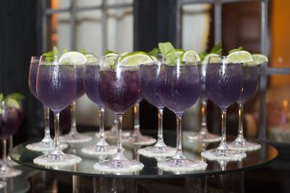wedding-reception-with-a-display-of-violet-drinks-limes-in-stemmed-glassware
