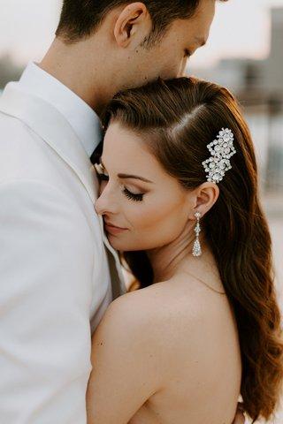 bride-portrait-with-groom-white-jacket-pretty-makeup-side-part-long-hair-headpiece-earrings