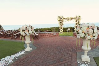 red-brick-path-with-white-flower-petals-and-flower-chuppah