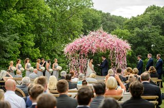 wedding-ceremony-in-countryside-greenery-pink-and-white-little-flowers-on-ceremony-structure