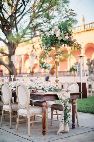 wooden-wedding-reception-table-with-blush-runner-covered-in-greenery