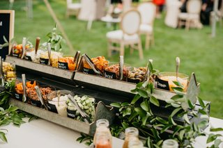 outdoor-wedding-reception-garden-party-salad-bar-with-bacon-cheddar-cheese-and-more-in-glass-jars