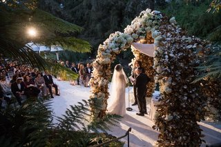 bride-in-veil-and-wedding-dress-saying-vows-under-chuppah-flower-in-bel-air-sunlight-streaming-in