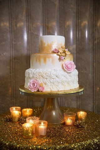 white-wedding-cake-with-rosettes-covering-one-layer-gold-brustrokes-on-the-other-two-pink-gold