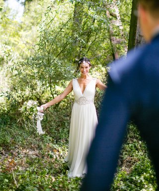 back-of-grooms-navy-blue-suit-walking-toward-bride-in-forest-v-neck-wedding-dress-first-look