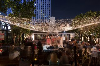 wedding-guests-at-outdoor-reception-lounge-area-just-married-settee-twinkle-light-canopy-downtown-la