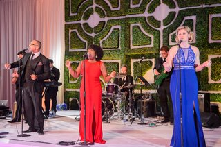wedding-reception-entertainment-live-band-singers-in-red-blue-evening-gowns-hedge-wall