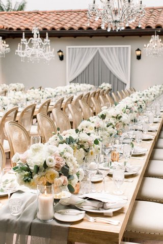 wedding-reception-terrace-cane-back-chairs-wood-table-low-white-pink-rose-ranunculus-centerpieces