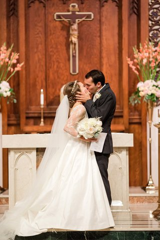 bride-and-groom-kiss-in-front-of-altar-at-catholic-church