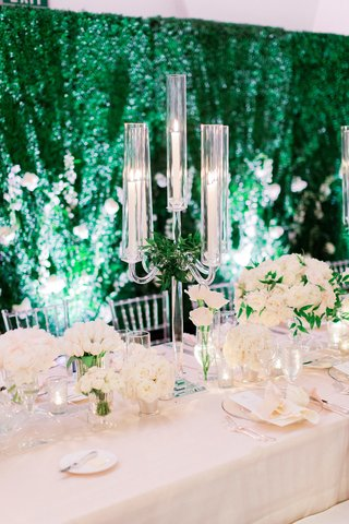 wedding-head-table-in-front-of-hedge-wall-with-ivory-flowers-and-crystal-candelabra-with-greenery