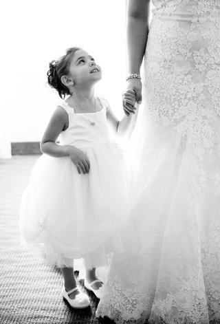 black-and-white-photo-of-flower-girl-looking-up-at-bride-joe-panik-and-brittany-pinto-wedding