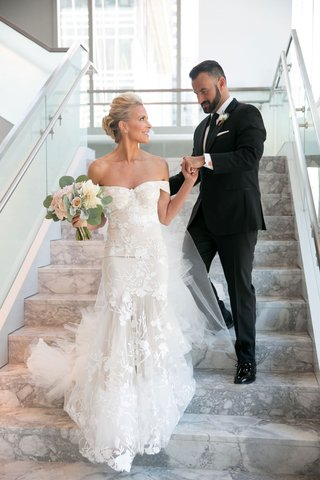 bride-brittany-daniel-actress-in-off-shoulder-form-fitting-wedding-dress-groom-in-suit-and-tie-stair