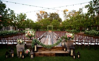 raised-platform-jewish-wedding-ceremony-greenery-small-candles-lanterns-alfresco