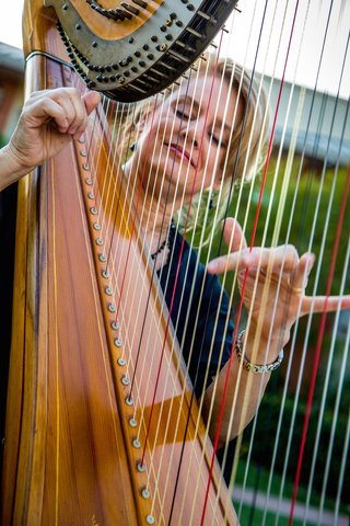 blonde-woman-plucking-harp-strings-at-ceremony