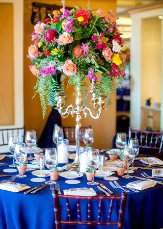 round-navy-tablescape-vibrant-florals-tall-arrangement-silver-candelabrum-spanish-flair-wedding