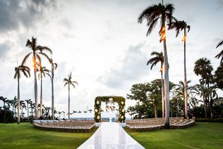 wedding-ceremony-grass-lawn-palm-trees-raised-aisle-seating-in-the-round