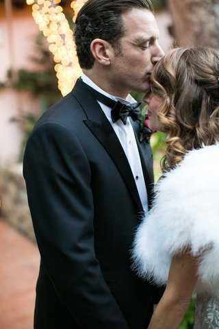 bride-in-wedding-dress-and-white-fur-stole-wrap-smiles-as-groom-in-tuxedo-kisses-her-forehead