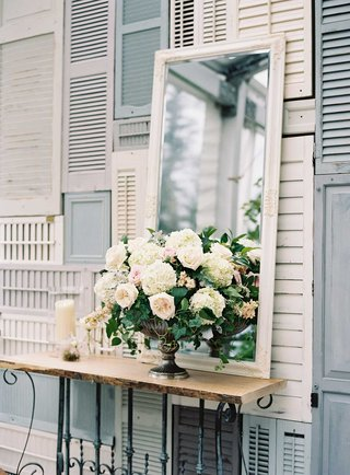 shabby-chic-wedding-outdoor-with-wall-of-white-and-blue-shutters-flower-arrangement-mirror-candles