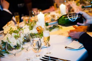 server-pours-champagne-into-wine-flute-for-guest-at-a-wedding-reception-table-with-light-flowers