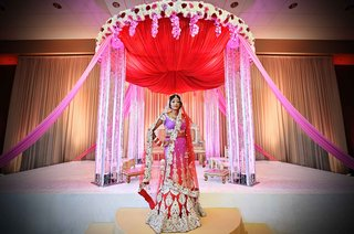 indian-bride-in-red-and-pink-sari-in-front-of-red-altar