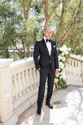 groom-on-staircase-with-white-flowers-tuxedo-tom-ford-bow-tie-white-pocket-square