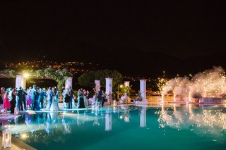 wedding-guests-dancing-outdoor-venue-reception-fireworks-going-off-pyrotechnics-at-wedding