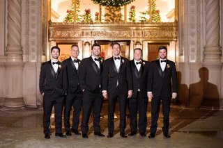 groom-and-groomsmen-in-three-piece-suit-tuxedos-bow-ties-in-front-of-altar-wedding-ceremony-church