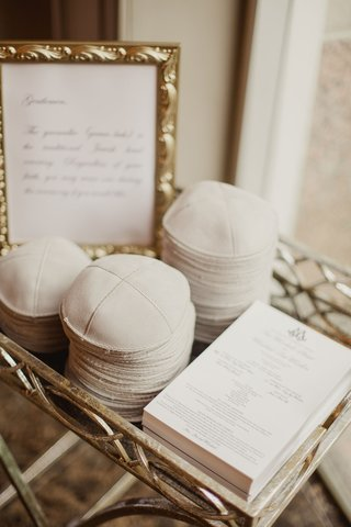 wedding-ceremony-program-and-yarmulkes-with-sign-in-gold-frame-in-tray-at-wedding-ceremony-jewish