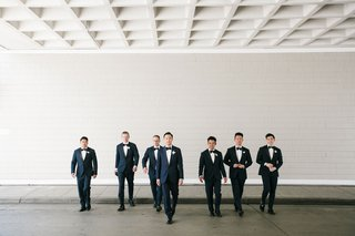 groom-and-groomsmen-walking-toward-camera-with-bow-ties-and-boutonnieres