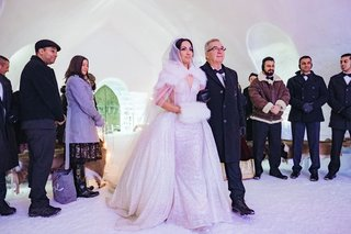bride-in-sparkle-wedding-dress-overskirt-with-fur-hand-muff-and-cape-walking-with-father-guest-coats