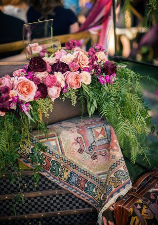 outdoor-bohemian-wedding-ceremony-with-tapestry-antique-luggage-peach-pink-red-roses-greenery