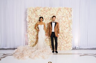 bride-in-inbal-dror-mermaid-gown-groom-in-bronze-patterned-tuxedo-jacket-ivory-blush-floral-wall