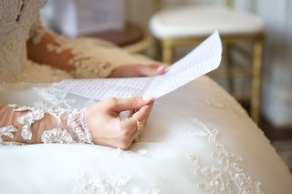 bride-in-ball-gown-illusion-sleeves-pearl-embellishments-reading-handwritten-note