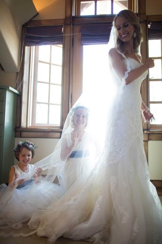 flower-girls-play-under-brides-veil-bride-smiling-flower-crowns-sash-dresses