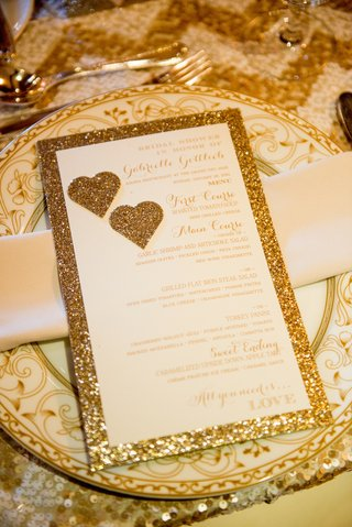 wedding-shower-menu-with-golden-glitter-border-and-hearts-on-china-chargers-with-florid-pattern